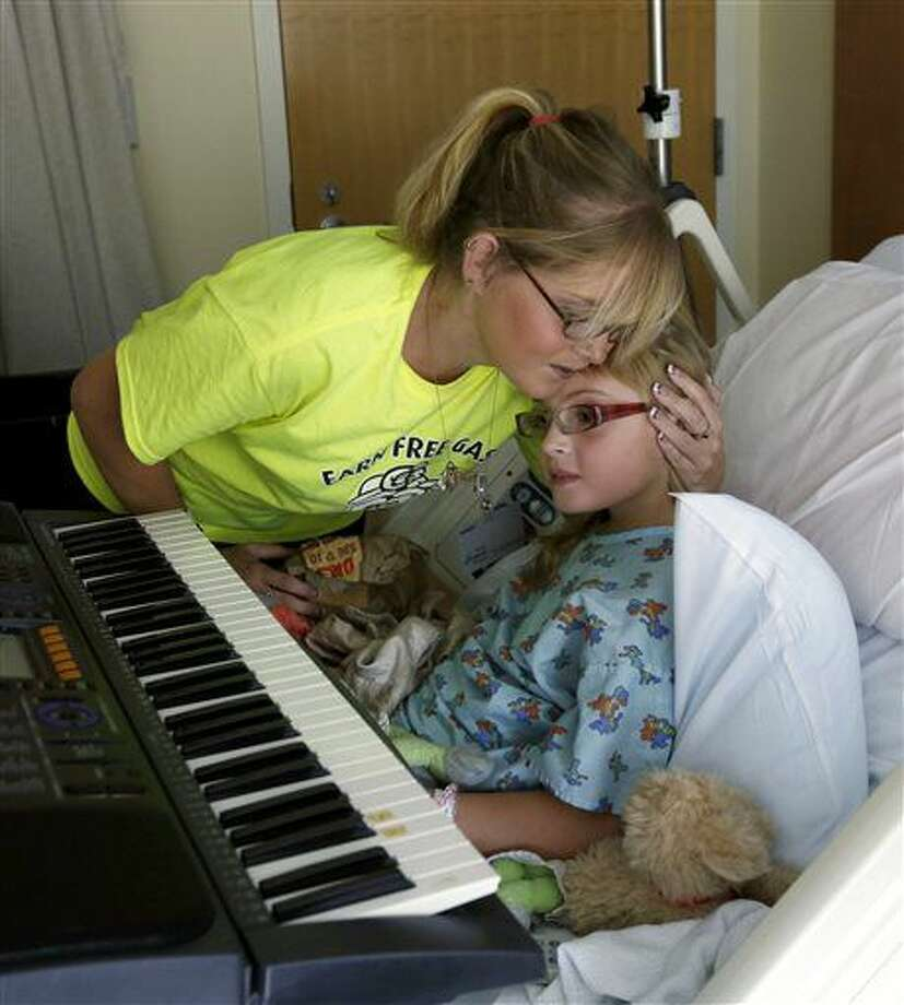 In a Sept. 9, 2016 photo, Grand Rapids, Ohio resident Heather Gorham kisses her daughter Hannah Gorham, 9, before she learns to play guitar with music therapist David Putano at the the ProMedica Toledo Children's Hospital Toledo,Ohio. In ProMedica Toledo Children's Hospital since Aug. 31 for severe migraines, Hannah was introduced recently to music therapy, a growing practice for hospitalized children and those with developmental or physical disabilities. (Lori King/The Blade via AP)