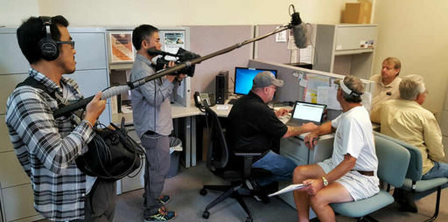In this photo taken on Sept. 15, 2016, a Japanese television crew from NHK-TV interviews unemployed coals miners at the CareerLink office in Waynesburg, Pa., about their new job prospects. The plight of Greene County's mining industry was the focus of numerous documentaries in recent months, including ones produced by journalists from Israel, Australia, Germany and France. (Mike Jones/Observer-Reporter via AP)