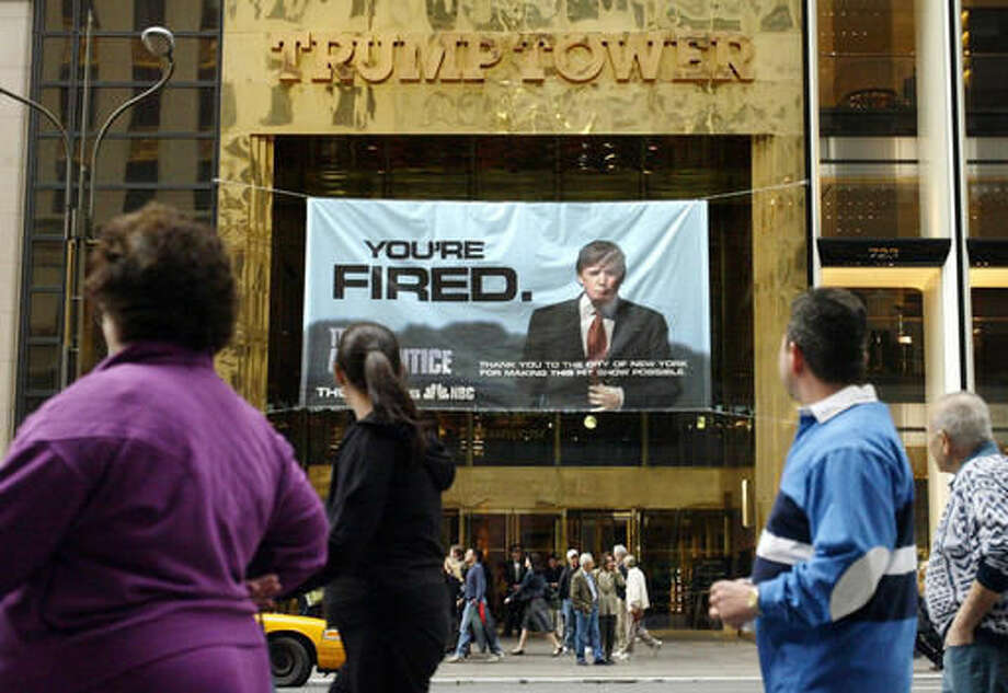 "FILE - In this Saturday, March 27, 2004 file photo, passersby look at a sign advertising the reality television show, ""The Apprentice,"" displayed at the entrance to the Trump Tower building in New York. Donald Trump's development firm was issued summonses by the city because it did not have the proper permits for the giant banner. In his years on the show, Trump repeatedly demeaned women with sexist language, according to show insiders who said he rated female contestants by the size of their breasts and talked about which ones he'd like to have sex with. (AP Photo/Bebeto Matthews)"