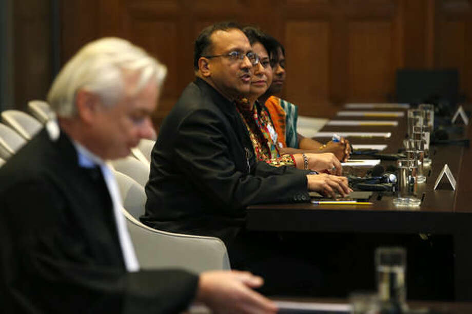 Phon van den Biesen, lawyer for the Marshall Islands, left, India's Ambassador J.S. Mukul, third right, and other representatives of the Indian delegation wait for the start of the World Court session in The Hague, Netherlands, Wednesday, Oct. 5, 2016, where the Marshall Island are taking India, Pakistan and the U.K. to court to urge those powers to resume negotiations to eradicate the world's nuclear stockpile. (AP Photo/Peter Dejong)