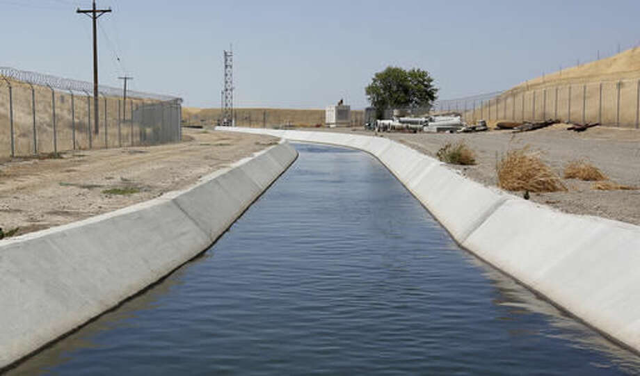 FILE - In this Tuesday, July 21, 2015 file photo, water flows down a diversion canal operated by the Byron-Bethany Irrigation District, near Byron, Calif., that is drawn out of a channel leading to to the William O. Banks pumping plant. State regulators said Wednesday, Oct. 5, 2016, water conservation continues to slip in drought-stricken California after officials lifted mandatory cutbacks. (AP Photo/Rich Pedroncelli, File)