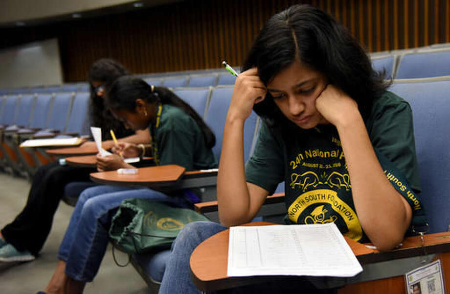 In this Saturday, Aug. 20, 2016, photo, Akshra Paimagam, of Charlotte, N.C., looks over her work as she competes in Phase 1 of the Senior Spelling Bee during the North South Foundation Finals in Tampa, Fla. The last dozen winners of the Scripps National Spelling Bee have been Indian-American. They share more than heritage. All 12 have participated in the nonprofit North South Foundation's annual spelling bee for children of Indian descent. (AP Photo/Jason Behnken)