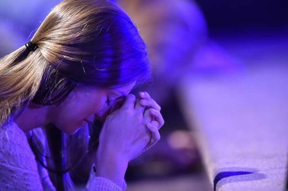 A worshiper prays at the altar during a service at River Point Community Church before baptisms in the Chattahoochee River, Sunday, Sept. 18, 2016, near Demorest, Ga. (AP Photo/Mike Stewart)