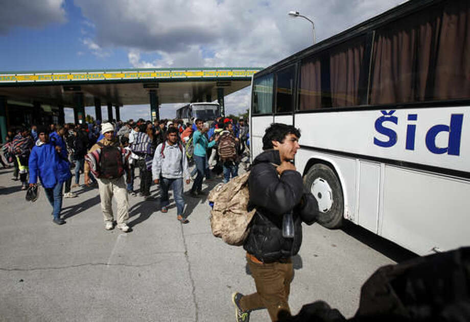 Migrants board a bus at a local gas station near the town of Indjija, about 40 kilometers (24 miles) north of the Belgrade, Serbia, Wednesday, Oct. 5, 2016. More than one hundred migrants who set off on foot toward the Hungarian border have agreed to end their protest march, demanding the border to be opened, and return to the Serbian capital of Belgrade after spending the night out in the open. (AP Photo/Darko Vojinovic)