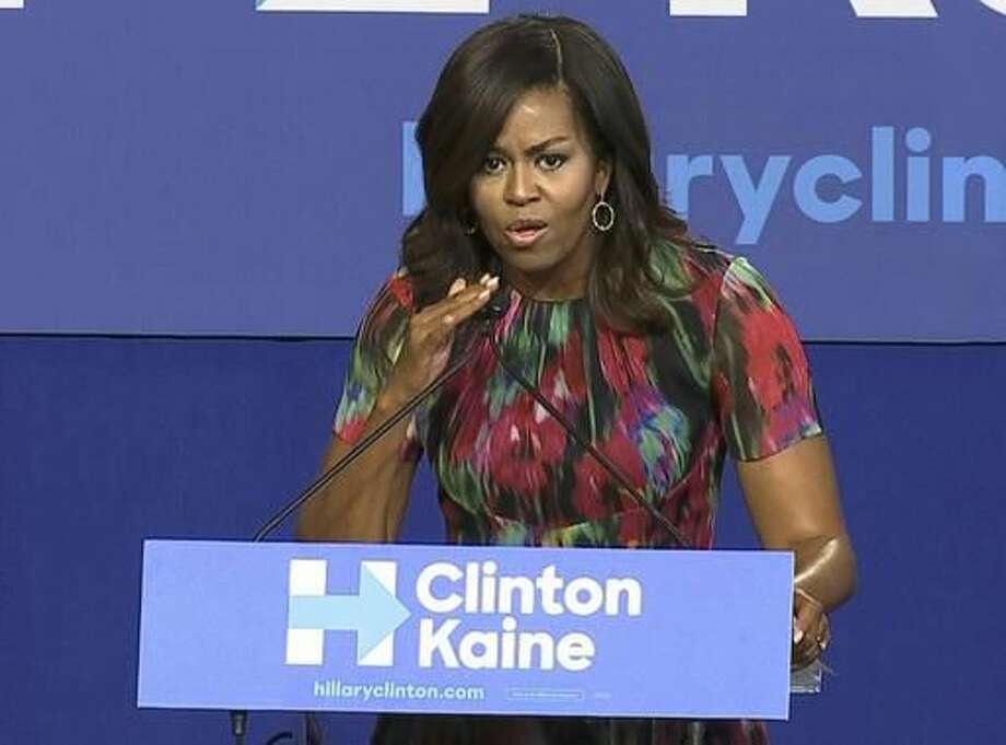 """In this image from video, first lady Michelle Obama taps a microphone as she speaks during a campaign rally for Democratic presidential candidate Hillary Clinton, Tuesday, Oct. 4, 2016, in Charlotte, N.C. She didn't mention Donald Trump by name, but Michelle Obama delivered a clear indictment of the Republican presidential nominee during a campaign event for Democratic nominee Hillary Clinton. Praising Clinton, Mrs. Obama said, """"She doesn't cry foul"""" and tapped her microphone. It was an apparent swipe at Trump, who said the microphone he used during the first presidential debate was defective. (AP Photo/Alex Sanz)"""