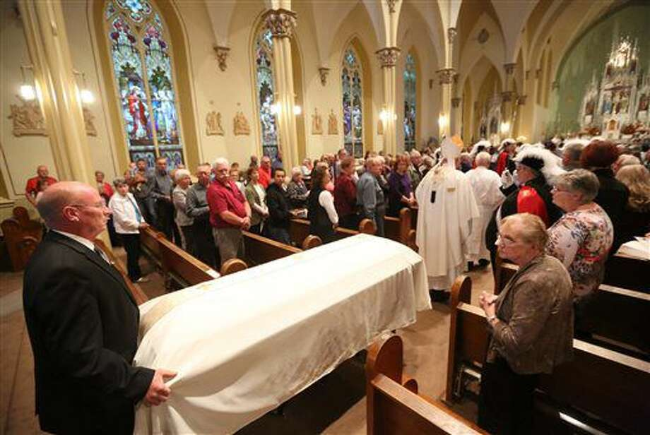 Pat Leonard, far left, escorts the casket during a Mass of remembrance for Chaplain Aloysius Schmitt on Wednesday, Oct. 5, 2016, at St. Luke's Church in St. Lucas, Iowa. Schmitt, a St. Lucas, native, died on Dec. 7, 1941, when the Japanese attacked Pearl Harbor. After nearly 75 years, his remains have been identified. (Jessica Reilly/Telegraph Herald via AP)