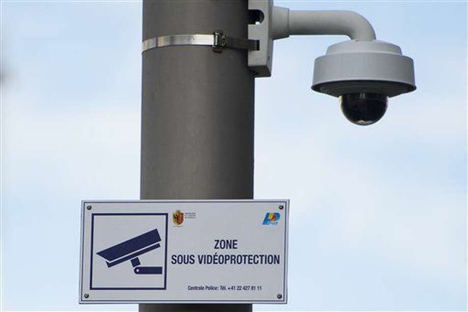 FILE - The Oct. 14, 2014 file photo shows a surveillance camera and a sign indicating the surveillance zone in the neighborhood of Paquis close to the central train station in Geneva, Switzerland. On Sept. 25, 2016 Swiss voters are casting ballots to decide whether to grant new powers to Switzerland's intelligence services, such as tracking internet activity, snooping on email boxes and tapping phones to better fight spies, criminal hackers and violent extremists. (Jean-Christophe Bott/Keystone via AP)