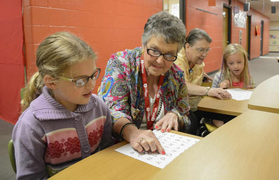 ADVANCE FOR USE SATURDAY, SEPT. 17 - In this Sept. 8, 2016 photo, second grade student Samantha Leisse, 7, left, gets some one-on-one time with foster grandmother Mollie Decker, while fellow foster grandmother Mary Hoke helps second grader Karley Weiser, 7, at Beck Elementary School in Sunbury, Pa. (Robert Inglis/The Daily Item via AP)