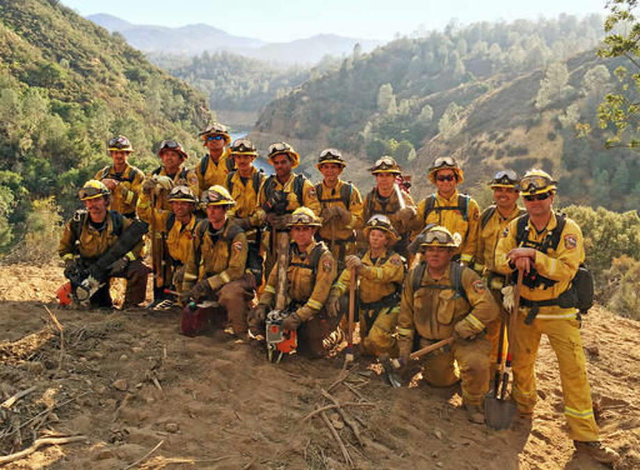 In this Aug. 15, 2016 photo provided by the California Conservation Corps, a civilian firefighter crew poses for a group photo during their deployment on the Chimney Fire in San Luis Obispo County, Calif. California officials faced with a shrinking pool of inmate firefighters during major blazes are increasingly turning to the California Conservation Corps. The program reopened a camp this year to train multiple crews of young civilian firefighters to do the same backbreaking work as inmates. (California Conservation Corps via AP)