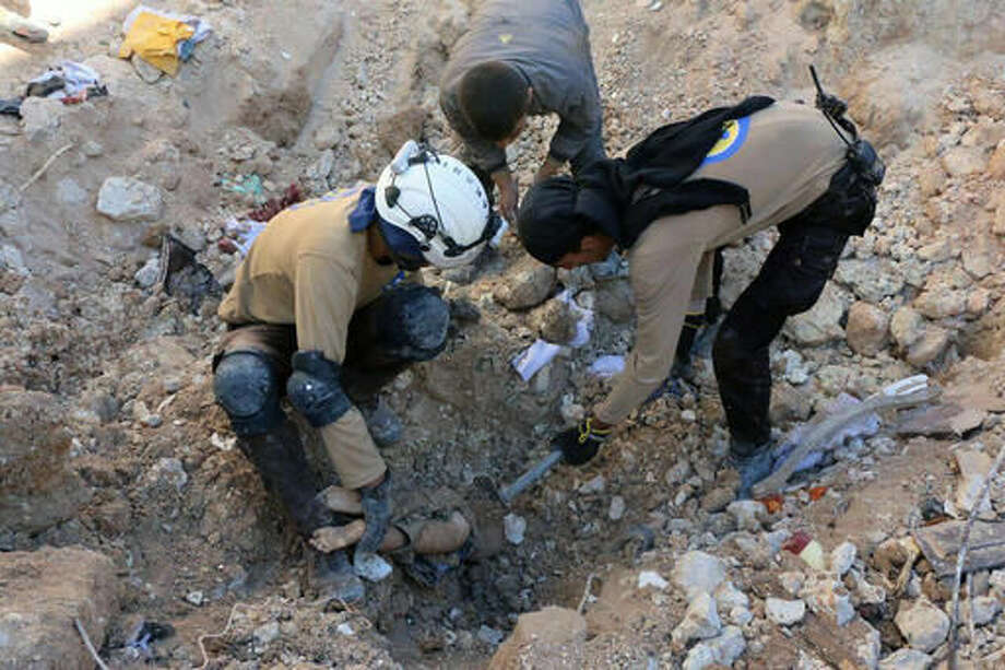 In this photo provided by the Syrian Civil Defense group known as the White Helmets, shows members of Civil Defense removing a dead body from under the rubble after airstrikes hit in Aleppo, Syria, Saturday, Sept. 24, 2016. Syrian government forces captured a rebel-held area on the edge of Aleppo on Saturday, tightening their siege on opposition-held neighborhoods in the northern city as an ongoing wave of airstrikes destroyed more buildings. (Syrian Civil Defense White Helmets via AP)
