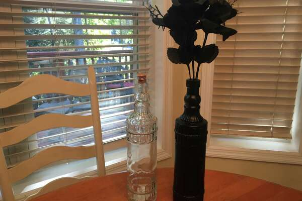 I found this neatly-shaped, clear corked bottle at Dollar Tree. I spray-painted the bottle black with a can I had on hand. I popped a sprig of faux black flowers ($1 at Dollar Tree) for a Halloween-themed arrangement.
