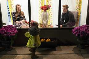 Northwood University students Allison Brown, 20, and Troy Cini, 19, react while modeling as mannequin as Sawyer Govitz, 2, of Midland, waves from on the sidewalk during Mannequin Night in Downtown Midland on Thursday. Mannequin Night is sponsored by the Northwood University Fashion Marketing & Management Department and the Midland Downtown Business Association.