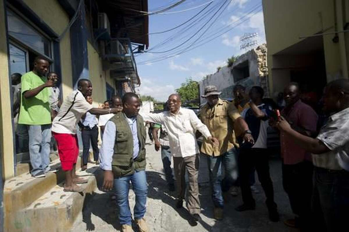 In this Sept. 21, 2016 photo, Haiti's former President Jean-Bertrand Aristide, center, greets supporters as he campaigns with presidential candidate Maryse Narcisse, of the Fanmi Lavalas political party, in Port-au-Prince, Haiti. Former President Jean-Bertrand Aristide has leaped from behind the scenes to take a role in presidential campaigning in Haiti, leading many to believe the most polarizing figure in Haitian politics is poised to regain influence if his party wins the Oct. 9 elections. (AP Photo/Dieu Nalio Chery). ( AP Photo/Dieu Nalio Chery)
