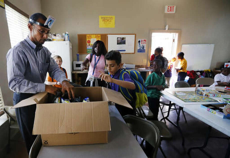 Miguel Moll, left, hands out snacks to children arriving to an after school program at an apartment complex, Friday, Sept. 2, 2016, in Fort Worth, Texas. Moll knew the risk of rape when he was thrown into a Texas jail in 1989 after joyriding in a stolen car. A generation later, the federal government has adopted guidelines intended to prevent prison rape in part by separating young offenders from adult inmates. (AP Photo/Tony Gutierrez)