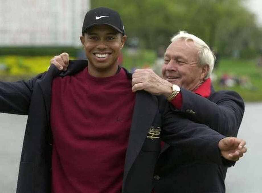 """File-This March 18, 2001, file photo shows Tiger Woods, left, being helped into his jacket for winning the Bay Hill Invitational by tournament host Arnold Palmer in Orlando, Fla. Woods Palmer, who made golf popular for the masses with his hard-charging style, incomparable charisma and a personal touch that made him known throughout the golf world as """"The King,"""" died Sunday, Sept. 25, 2016, in Pittsburgh. He was 87. (AP Photo/Scott Audette, File)"""