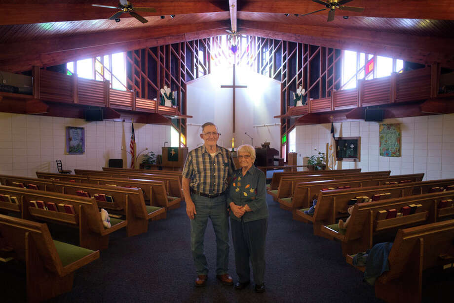 LEFT: Poseyville United Methodist Church members Don Reid, left, and Jennie Cron both have attended the church for more than 70 years. This Sunday the church is celebrating its 125th anniversary. ABOVE: A hand-sewn quilt hangs inside the Poseyville United Methodist Church. Members of the congregation made the different squares of the quilt.