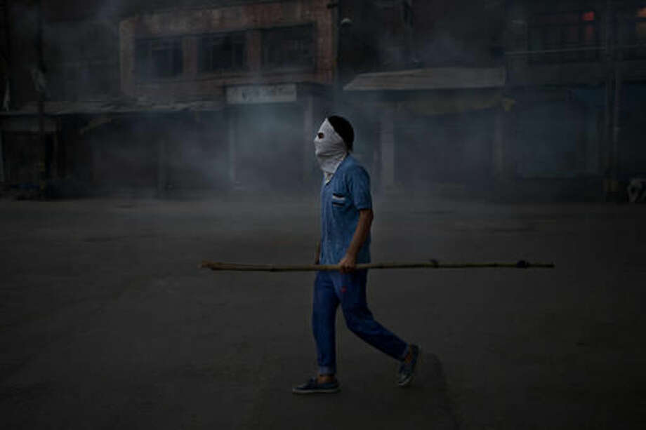 "A Kashmiri Muslim protester holds a bamboo stick as stands in tear gas smoke during a protest after funeral prayers in absentia for Pakistani soldiers killed in cross border firing in Srinagar, Indian controlled Kashmir, Thursday, Sept. 29, 2016. Pakistan on Thursday said two of its soldiers were killed in an ""unprovoked"" attack when India fired across the border of the disputed region of Kashmir, while India said it had carried out a ""surgical strike"" against terrorists, in an exchange that marks an escalation in tensions between the uneasy and nuclear-armed neighbors. Pakistan and India often trade fire in Kashmir, a Himalayan region that is split between the two countries and claimed by both in its entirety. (AP Photo/Dar Yasin)"