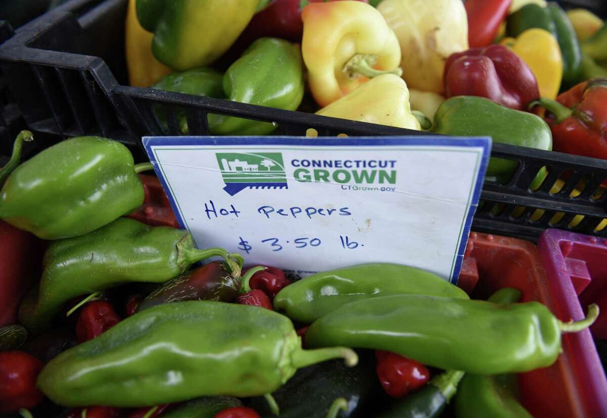 Hot peppers, below, and colorful sweet peppers are displayed at Niantic's Smith's Acres stand at the Old Greenwich Farmer's Market in Old Greenwich, Conn. Wednesday, Sept. 21, 2016. The farmer's market is held at the Presbyterian Church of Old Greenwich every Wednesday from 2:30 p.m. to 6 p.m. through the end of October, then from 2 p.m. to 5 p.m. in November. There are eight weekly vendors and several more guest vendors, all located in Connecticut, selling a variety of fruits, veggies, cheeses, bread, meat, flowers and more.