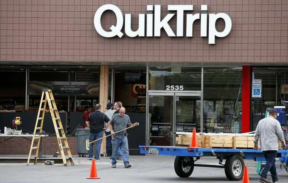 Construction workers continue cleaning up in front of a QuickTrip store hours after a driver plowed into two police officers Tuesday, Sept. 13, 2016, in Phoenix. Police said Marc LaQuon Payne, 44, apparently drove his vehicle at the officers before hitting a patrol car and crashing into the front of the store around 2 a.m. Tuesday. (AP Photo/Ross D. Franklin)
