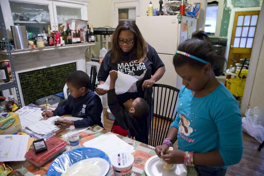 This Tuesday, Oct. 8, 2013 photo shows Jennifer Donald, whose family receives money from the Supplemental Nutrition Assistance Program also known as food stamps, looks at her son's Donovan, 4, drawing as his brother David, 6, left, does his home work and daughter Jayla, 10, helps prepare dinner in Philadelphia. Families already buffeted by difficult economic times will see their food stamps benefits drop Nov. 1 as money allocated by the 2009 federal stimulus plan runs out. The average family of four will see benefits drop by $36 a month, a tough hit at a time when child poverty is climbing and Congress is debating a major cut to the Supplemental Nutrition Assistance Program. (AP Photo/Matt Rourke)