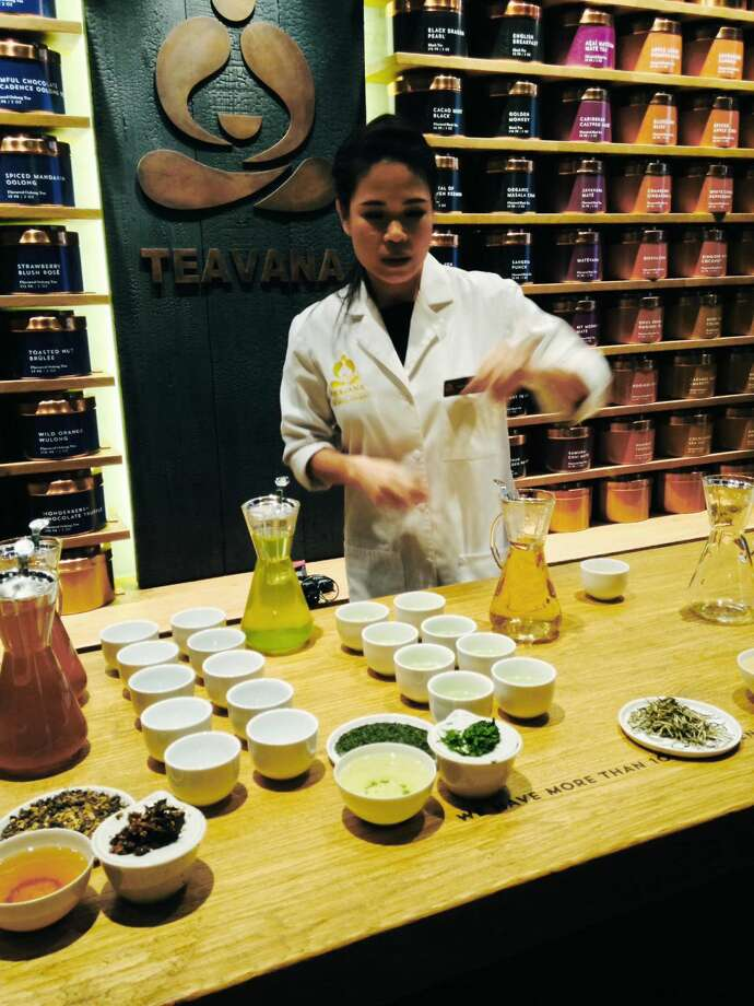 A Starbucks employee shows the new Teavana 'tea bar' in New York during a media event on Wednesday, Oct. 23, 2013. Starbucks plans to open its first Teavana 'tea bar' in New York on Thursday. The company says it plans to make tea popular in the U.S. as coffee. (AP Photo/ Candice Choi)