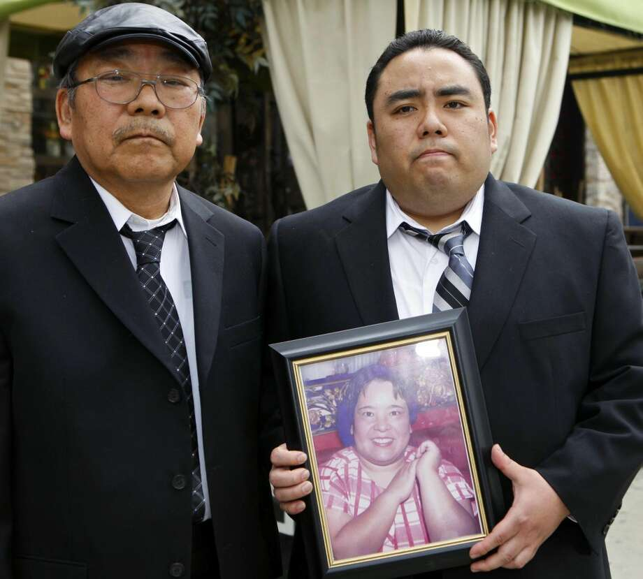 "This Thursday, Feb. 4, 2010 file photo shows Jeffrey Uno, right, and his father, Peter Uno, the son and husband of Noriko Uno, in framed photo, who died in an alleged ""sudden unintended acceleration"" crash in a Toyota Camry in August 2009, in Los Angeles. A jury on Thursday Oct. 10, 2013 found Toyota not liable for death of Noriko Uno. (AP Photo/Damian Dovarganes, File)"