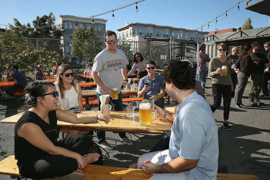 Thu Pham (left) and other students visiting from the University of North Caro lina drink in the sunshine at the Biergarten, an outdoor beer and food spot. Photo: Liz Hafalia, The Chronicle
