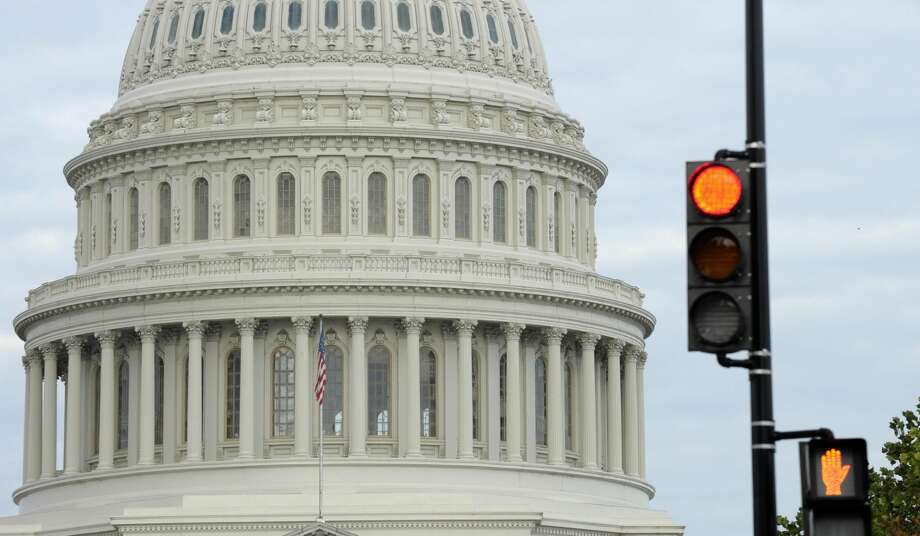 A stop light flashes near the Capitol in Washington, Tuesday, Oct. 1, 2013. Congress plunged the nation into a partial government shutdown Tuesday as a long-running dispute over President Barack Obama's health care law stalled a temporary funding bill, forcing about 800,000 federal workers off the job and suspending most non-essential federal programs and services. (AP Photo/Susan Walsh)