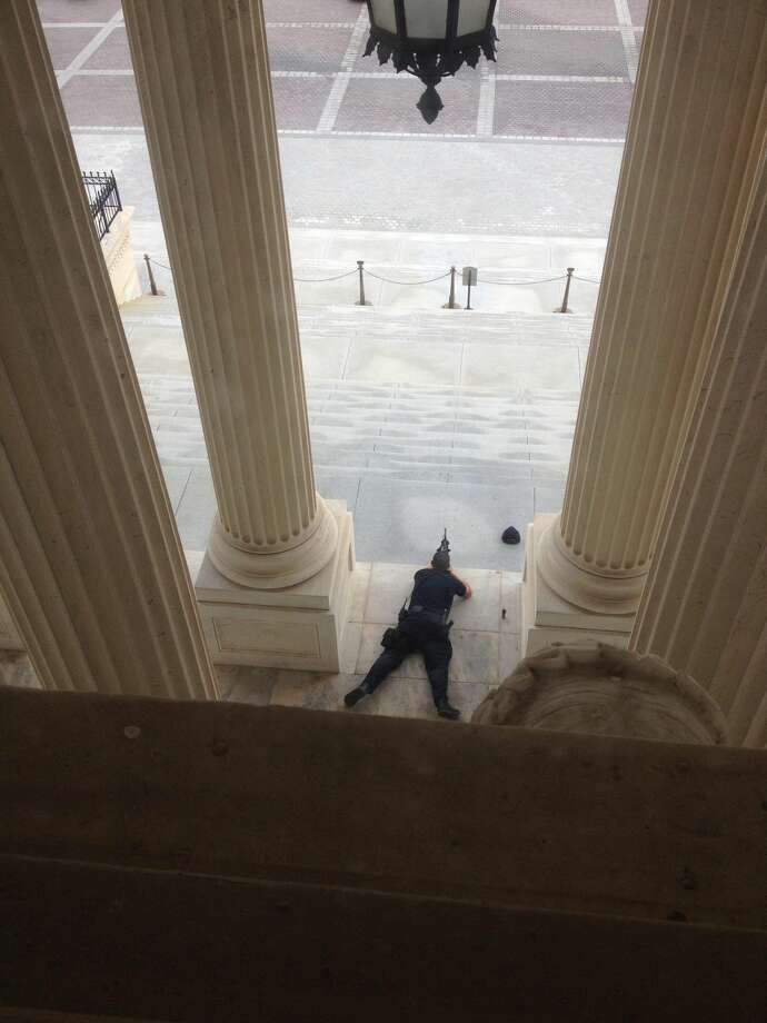 A U.S. Capitol police officer lies on the steps of the Senate with a gun drawn in response to a report of shots fired Thursday, Oct. 3, 2012. A police officer was reported injured after gunshots at the U.S. Capitol. They locked down the entire complex, at least temporarily derailing debate over how to end a government shutdown. (AP Photo/The Tampa Bay Times, Alex Leary)
