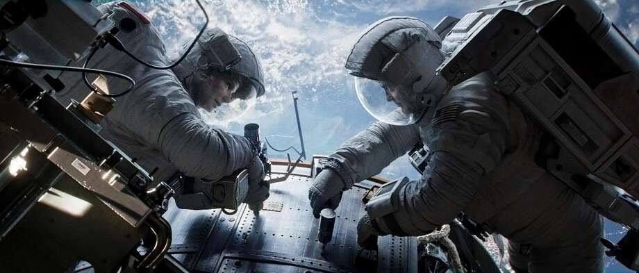 """This publicity photo released by Warner Bros. Pictures shows Sandra Bullock, left, as Dr. Ryan Stone and George Clooney as Matt Kowalsky in """"Gravity."""" (AP Photo/Courtesy Warner Bros. Pictures)"""
