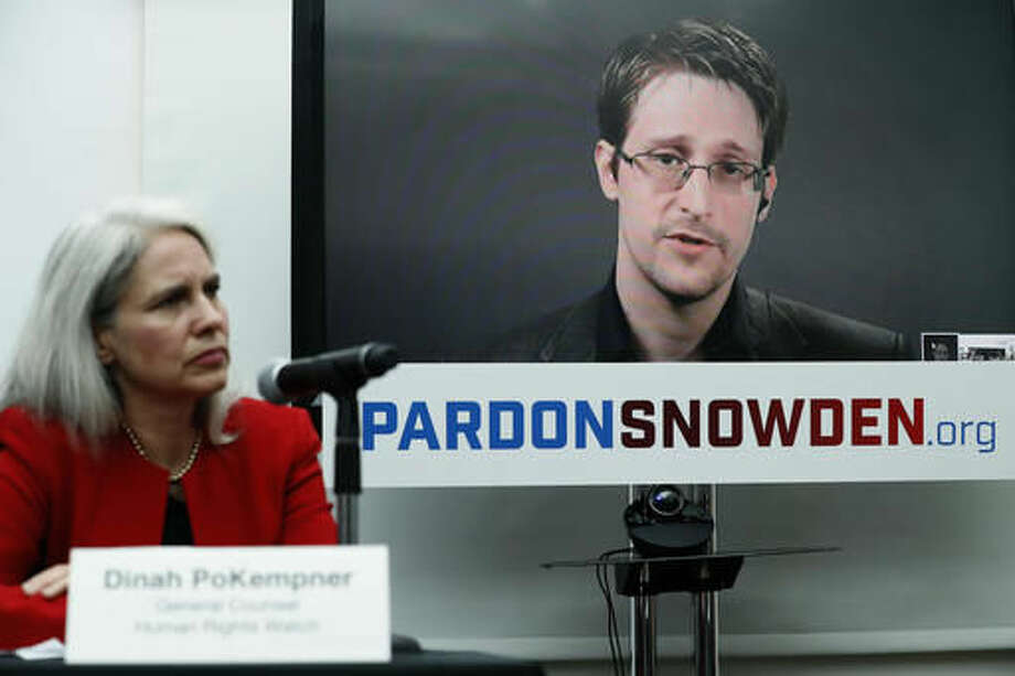 Dinah PoKempner, left, general council for Human Rights Watch, listens as Edward Snowden speaks on a television screen via video link from Moscow during a news conference to call upon President Barack Obama to pardon Snowden before he leaves office, Wednesday, Sept. 14, 2016, in New York. Human and civil rights organizations, including the ACLU, Human Rights Watch and Amnesty International, launched a public campaign to persuade Obama to pardon the former National Security Agency contractor, who leaked classified details in 2013 of the U.S. government's warrantless surveillance program before fleeing to Russia. (AP Photo/Mary Altaffer)