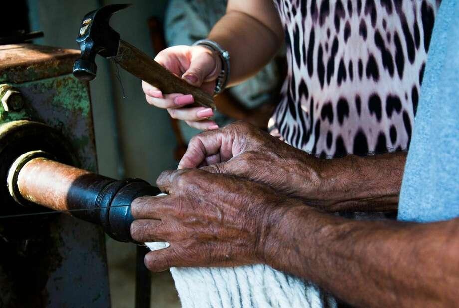 La imagen muestra las manos de la presidenta del patronato del Sistema DIF, Belinda Serna de Canturosas, mientras ayuda a un integrante de la Asociación de Invidentes Productivos a fabricar un trapeador. (Foto de cortesía)