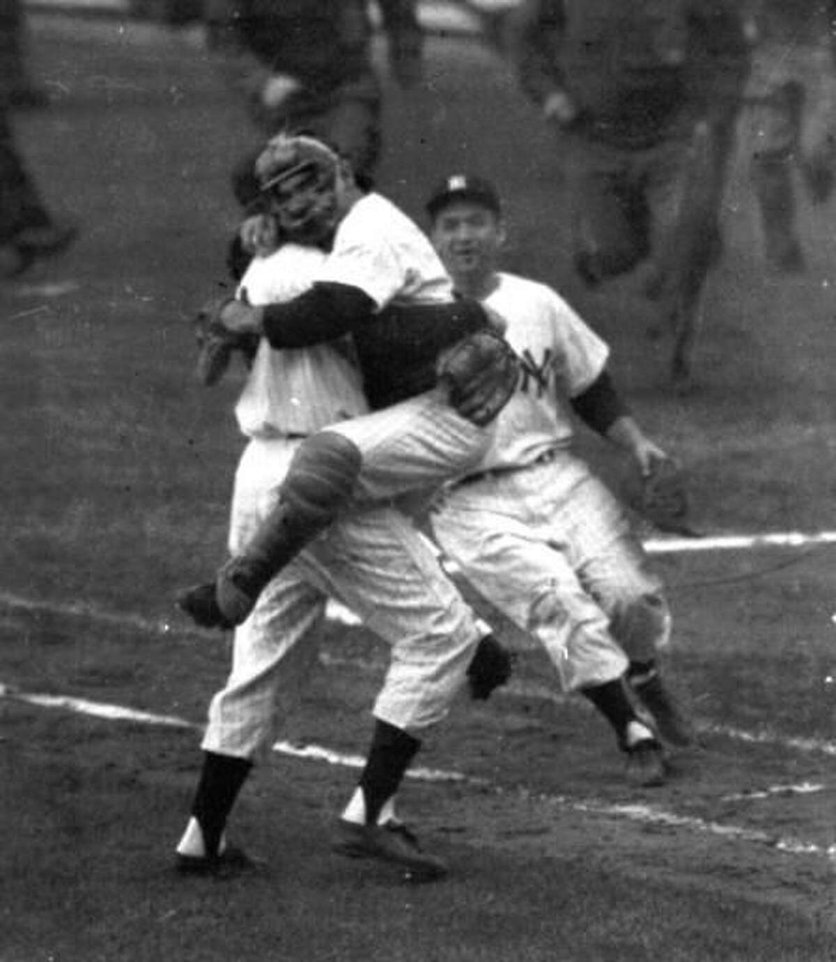 FILE- In this Oct. 8, 1956, file photo, New York Yankees catcher Yogi Berra is embraced by pitcher Don Larsen as he leaps into Larsen's arms at the end of Game 5 of baseball's World Series against the Brooklyn Dodgers at New York's Yankee Stadium. Larsen pitched a perfect game. The last go-round for the Los Angeles Dodgers' Hall of Fame announcer Vin Scully begins on Monday night, Sept. 19, 2016. The 88-year-old Scully has narrated some of the most memorable moments in baseball history since he began his career calling Brooklyn Dodgers games in 1950. (AP Photo, File)
