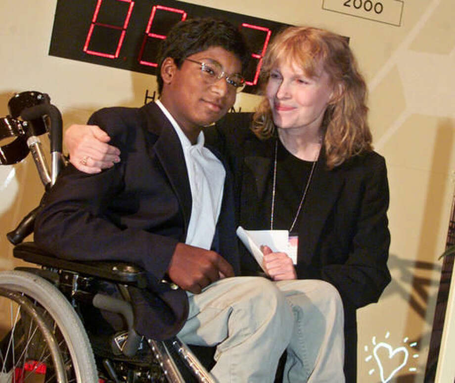 FILE - In this Sept. 27, 2000 file photo, actress Mia Farrow poses with her adopted son Thaddeus as they participate in the global summit on polio eradication at United Nations headquarters. Thaddeus Wilk Farrow, died, Wednesday, Sept 21, 2016, after being found seriously injured in his vehicle in Connecticut. The actress adopted Thaddeus, who contracted polio in an orphanage in Kolkata, India, and was paralyzed from the waist down. He was 27. (AP Photo/Richard Drew, File)