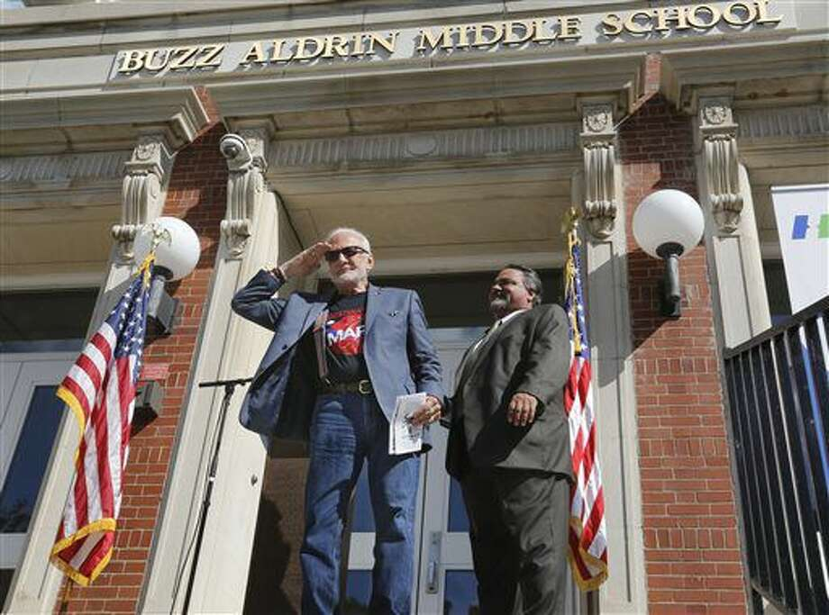 Apollo 11 astronaut Buzz Aldrin, left, salutes the crowd during the dedication ceremony of the Buzz Aldrin Middle School in Montclair, N.J., on Friday, Sept. 16, 2016. Mt. Hebron Middle School was officially renamed after the famous alumnus, the second man to step on the moon. (Patti Sapone/NJ Advance Media via AP)