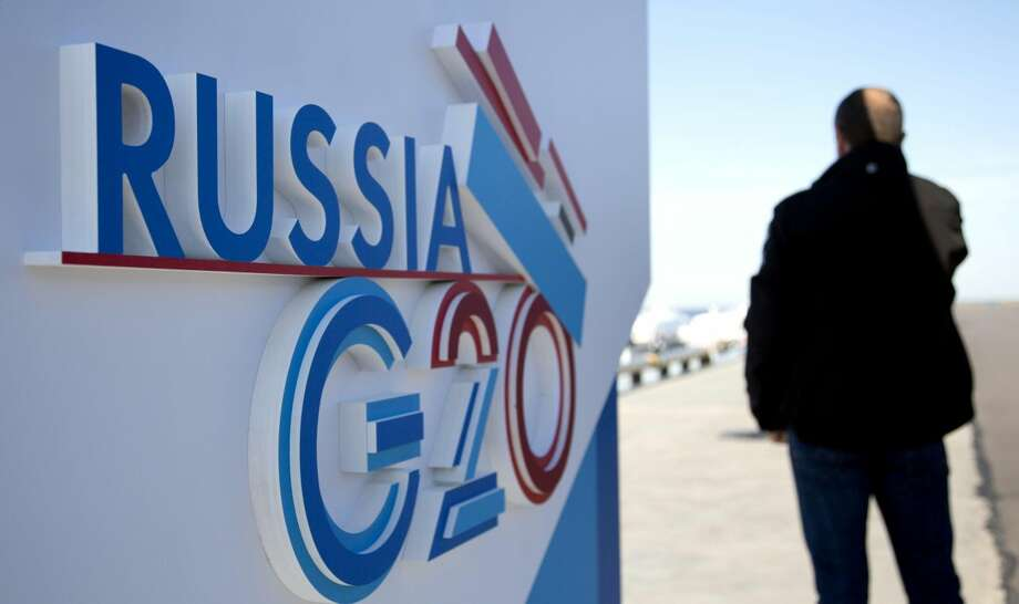 A journalist speaks on a cell phone next to a sign for the G20 summit in St. Petersburg, Russia on Wednesday, Sept. 4, 2013. The biggest economies, the United States, Europe, Japan, as well as China , are all expanding. And the leaders who will gather this week are more confident about their financial systems than at any time since they began meeting five years ago. (AP Photo/Virginia Mayo)