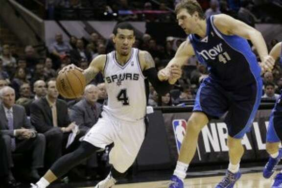 San Antonio Spurs' Danny Green (4) drives around Dallas Mavericks' Dirk Nowitzki (41) during the first half on a 2014 game in San Antonio. The Spurs won 112-90. (AP Photo/Eric Gay)