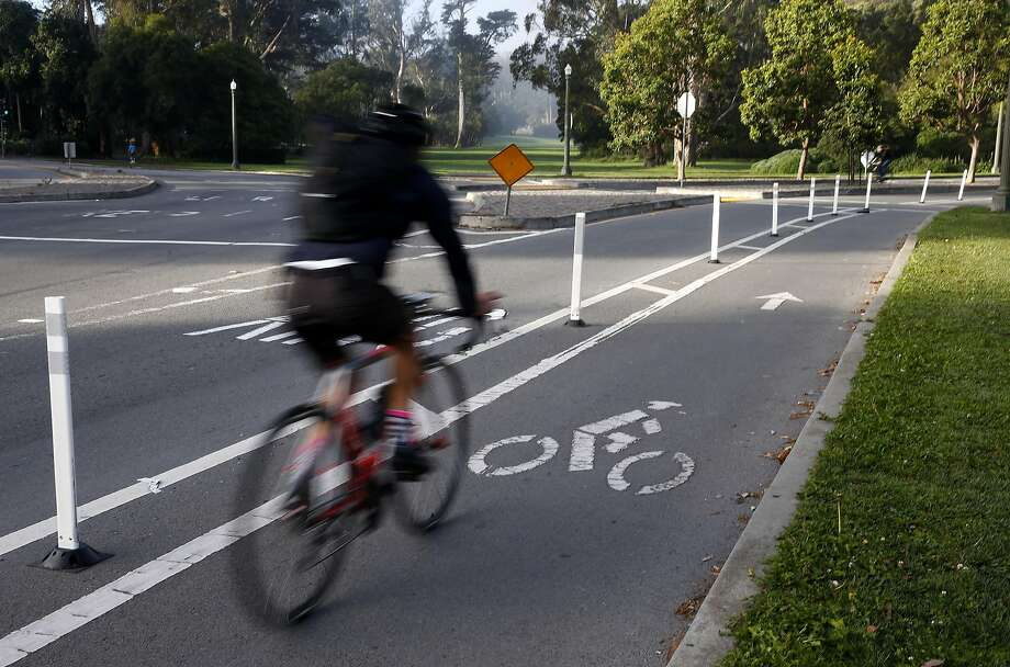 A  cyclist rides in a bike lane separated from traffic by flexible plastic posts on John F. Kennedy Drive in  Golden Gate Park in San Francisco. The posts were apparently installed illegally by so-called traffic safety vigilantes. Photo: Paul Chinn, The Chronicle