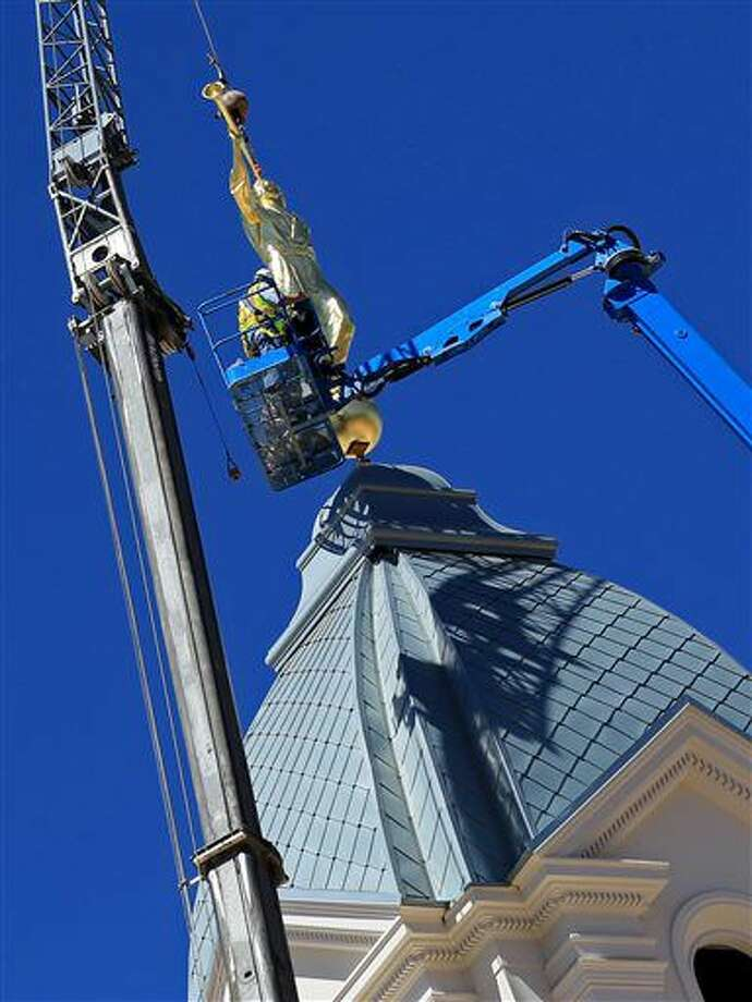 Construction workers place a statue of the Angel Moroni on top of the Cedar City Temple of The Church of Jesus Christ of Latter-day Saints on Thursday, Sep. 15, 2016 in Cedar City, Utah. The placement was initially delayed as even construction workers wanted their picture taken next to the statue.(The Spectrum & Daily News, Brian Passey via The AP)