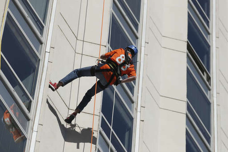Colorado Gov. John Hickenlooper rappels down a downtown high-rise as part of the Over The Edge fundraiser which benefits the Cancer League of Colorado, late Thursday, Sept. 8, 2016, in Denver. (AP Photo/David Zalubowski)