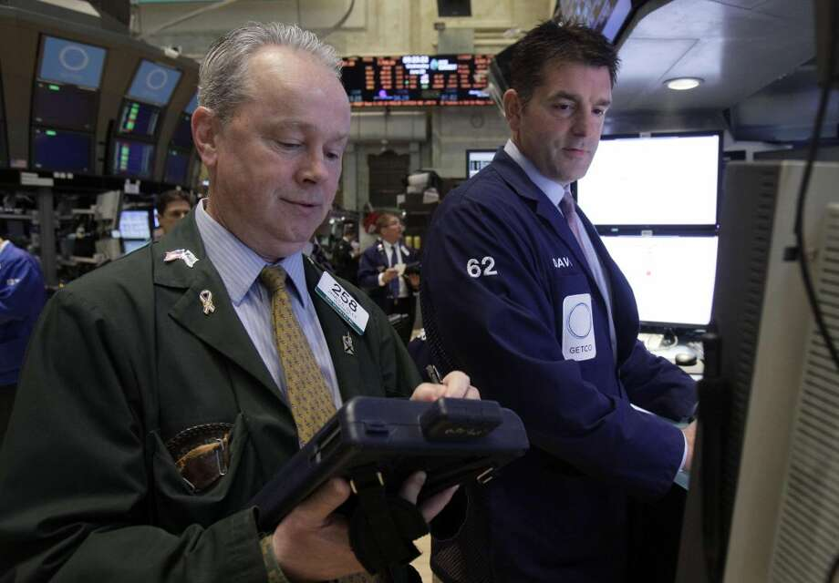 Trader James Riley, left, and specialist David Haubner work on the floor of the New York Stock Exchange on Wednesday. Stocks edged lower early Wednesday after investors saw signs that economies could be slowing down in both the West and China. (AP Photo/Richard Drew)