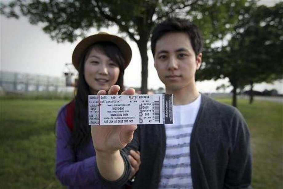 Jeongmi Lee and her boyfriend Mark Lee show their tickets as they leave Downsview Park after a stage collapsed prior to a Radiohead concert in Toronto, Saturday, June 16, 2012. The top of a stage being set up for a concert collapsed, killing one of the stage workers preparing for the event which was canceled. (AP Photo/The Canadian Press, Toronto Star, Tara Walton)