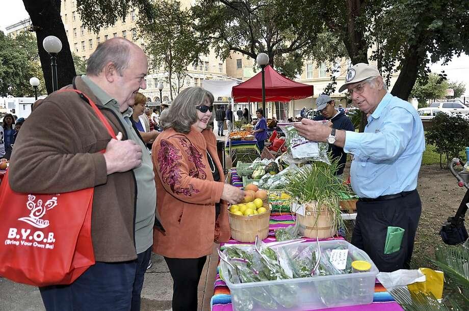 """George y Nancy Hughes compran algunos productos a Danny Gunn, en esta imagen de archivo acerca del Mercado Agrícola """"El Centro de Laredo"""". (Foto por Cuate Santos/LMT)"""