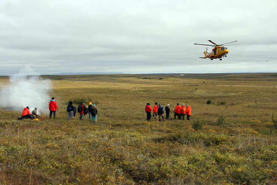 This Aug. 24, 2016, photo shows soldiers awaiting transport from a Canadian rescue helicopter during a mock exercise in Kotzebue, Alaska. The multinational cruise ship disaster drill with soldiers playing the role of passengers was held on Alaska's Bering Sea coast as the Crystal Serenity became the largest cruise ship to ever travel up the Bering Strait and continue east through the Northwest Passage en route to New York City. (AP Photo/Mark Thiessen)