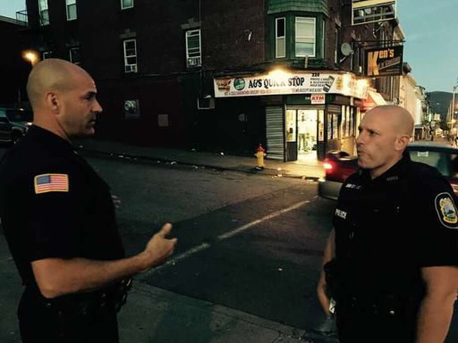 """In this Sept. 15, 2016, photo, Newburgh Police Officers Jeff Perez, left, and Chris Tabachnick talk outside a convenience store in Newburgh, N.Y., near the end of a foot patrol. New York is funding foot patrols in crime hotspots around the state with an emphasis on """"procedural justice,"""" where interactions are respectful and meant to be perceived as fair. It's part of an effort to cross a national divide between poor urban communities and law officers suspected of picking unfairly on minorities. (AP Photo/Michael Virtanen)"""
