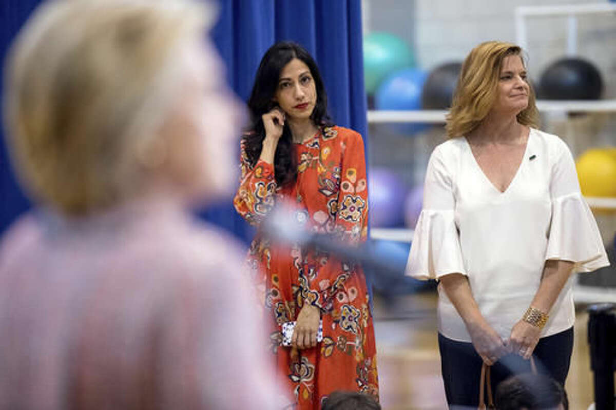 Senior aide Huma Abedin, center, and Director of Communications Jennifer Palmieri, right, stand nearby as Democratic presidential candidate Hillary Clinton answers a question from a member of the media after speaking at a rally at University of North Carolina, in Greensboro, N.C., Thursday, Sept. 15, 2016. Clinton returned to the campaign trail after a bout of pneumonia that sidelined her for three days and revived questions about both Donald Trump's and her openness regarding their health. (AP Photo/Andrew Harnik)