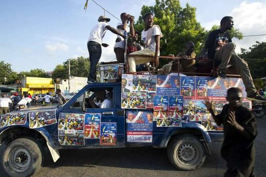 In this Sept. 21, 2016 photo, a truck is covered with campaign signs in favor of Haiti's former President Jean-Bertrand Aristide and presidential candidate Maryse Narcisse, of the Fanmi Lavalas political party, during a campaign event in Port-au-Prince, Haiti. While it's easy to find hardcore Lavalas supporters in neighborhoods that were once Aristide strongholds, roughly a third of Haiti's population is younger than 15 and only know his image from placards or paintings sold on roadsides. Haiti will hold elections on Oct. 9. (AP Photo/Dieu Nalio Chery)
