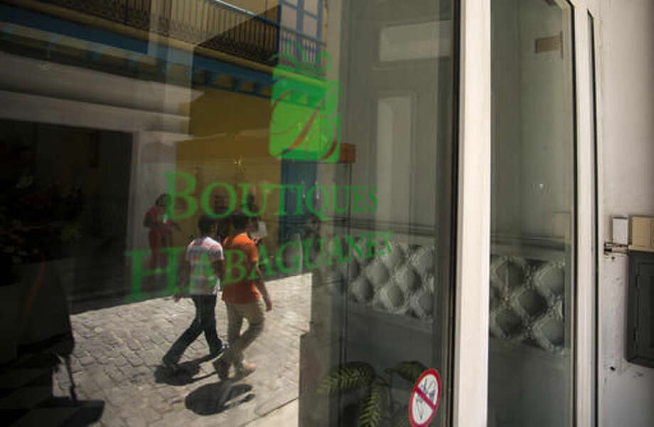 People are reflected on the door of a boutique of the Habaguanex company in Old Havana, Cuba, Thursday, Sept. 8, 2016. The largest business arm of the City Historian's Office, Habaguanex, named for a pre-Columbian indigenous chief, directly runs some 20 hotels and 30 stores and more than 25 restaurants in Old Havana. Last month, the Cuban military took over the business operations of the City Historian's Office, including Habaguanex. After Gen. Raul Castro became president in 2008, the armed forces became the prime beneficiary of a post-detente boom in tourism. (AP Photo/Desmond Boylan)