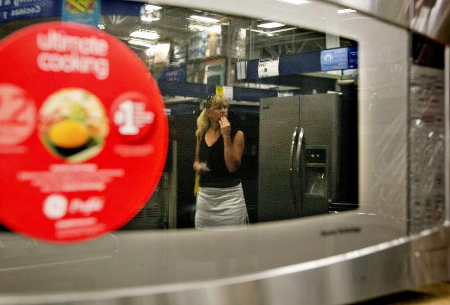 In this June 19, 2012 photo, a shopper is reflected in a microwave oven on display on a showroom floor at Lowe's store in Atlanta. Consumer confidence fell in June for the fourth month in a row as lingering worries about the economy outweighed relief at the gas pump, according to a private research group. (AP Photo/David Goldman)