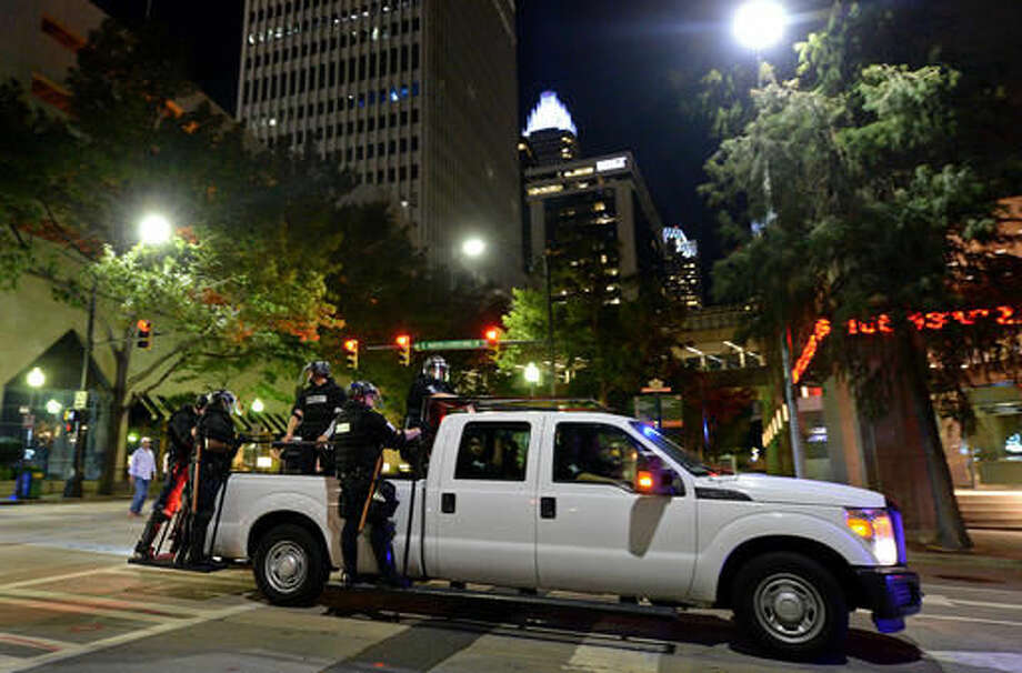 A pickup truck carries Charlotte police officers through the streets of the city as they follow demonstrators marching to protest Tuesday's fatal police shooting of Keith Lamont Scott, in Charlotte, N.C., Friday, Sept. 23, 2016. After darkness fell, dozens of people carried signs and chanted to urge police to release dashboard and body camera video that could show more clearly what happened. (Jeff Siner/The Charlotte Observer via AP)